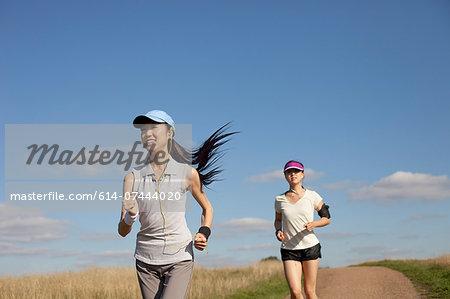 Two young women running along dirt track