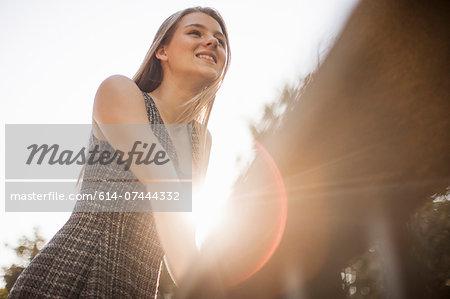 Teenage girl leaning on railings in park