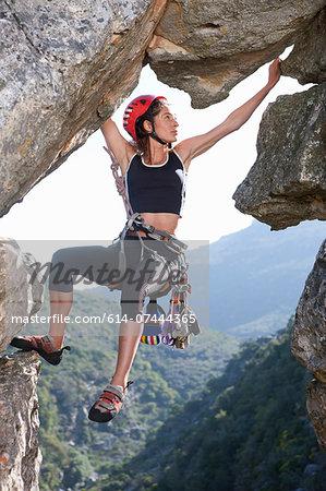Young female rock climber balancing on rock face