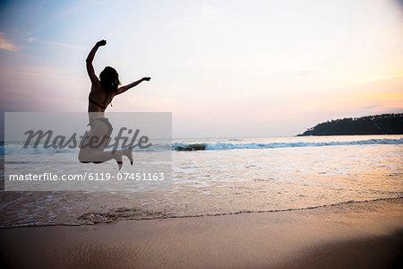 Tourist jumping on Mirissa Beach at sunset, South Coast of Sri Lanka, Southern Province, Sri Lanka, Asia