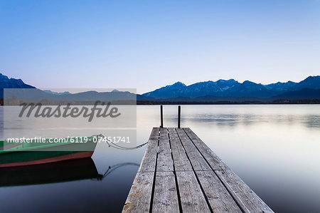 Rowing boat on Hopfensee Lake at sunset, near Fussen, Allgau, Allgau Alps, Bavaria, Germany, Europe