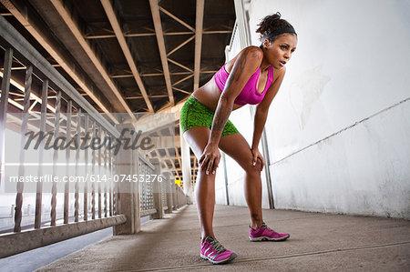 Young female runner taking a break on urban bridge