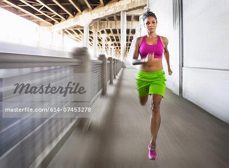 Blurred shot of young woman running on urban bridge