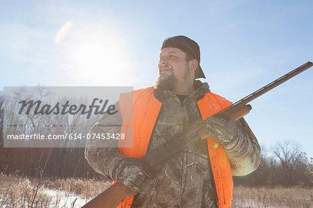 Mid adult man holding shotgun in Petersburg State Game Area, Michigan, USA