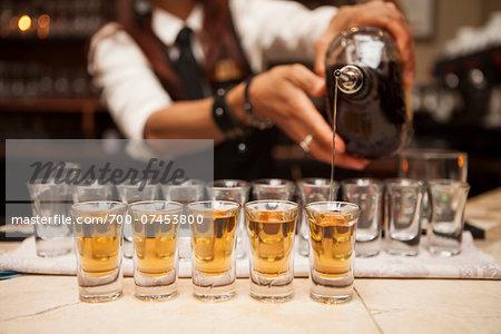 Close-up of man, bartender pouring alcohol into shot glasses, Toronto, Ontario, Canada