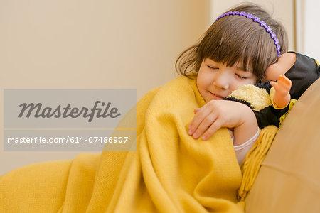 Young girl lying on sofa pretending to sleep