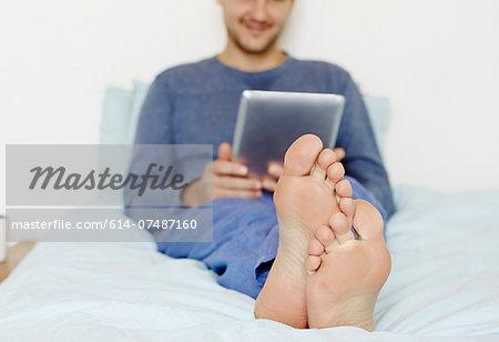 Mid adult man lying on bed using digital tablet