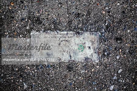 Still life of deteriorating one dollar bill on wet pavement