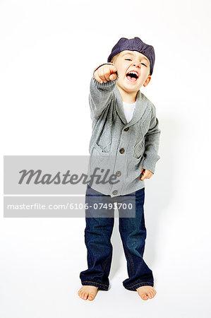 Three year old boy pointing into camera.