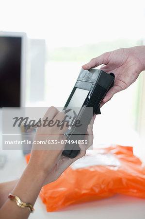 Woman writing signature on electronic device