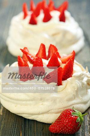 Pavlova dessert with strawberries and lemon cream on old wooden table.