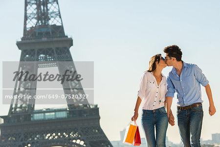 Young couple kissing near Eiffel Tower, Paris, France
