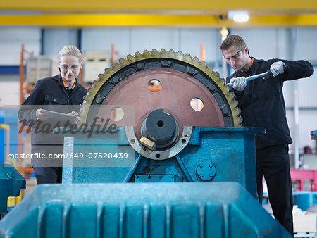 Engineers repair industrial gearbox in engineering factory