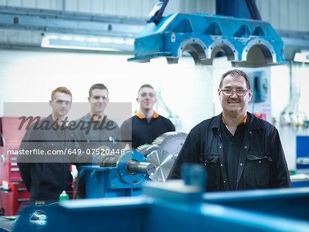Engineer teaching apprentices in engineering factory, portrait