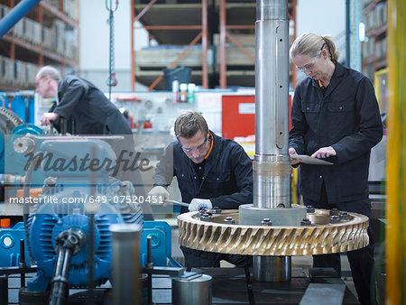 Engineers assembling industrial gearbox in engineering factory