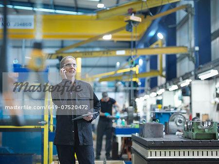 Female worker using mobile phone in engineering factory