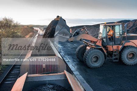 Diggers loading coal onto train at surface coal mine at dawn