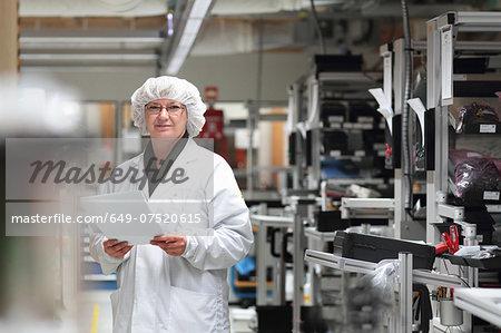 Female scientist holding paperwork in laser laboratory