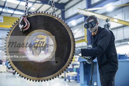 Engineer heat treats industrial gear in factory