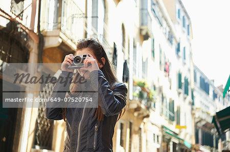 Girl taking photographs, Venice, Italy