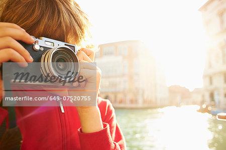 Young boy exploring with camera, Venice, Italy