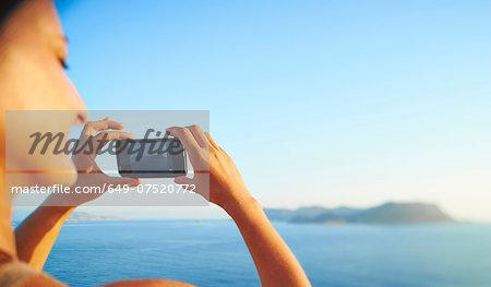 Mature woman checking photographs on smartphone, Kas, Turkey
