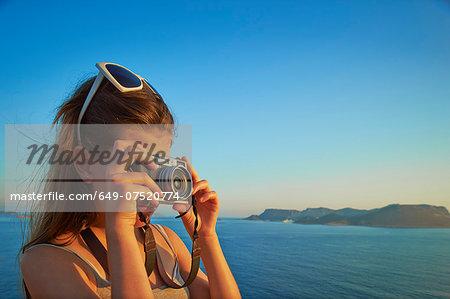 Girl taking photographs on holiday, Kas, Turkey