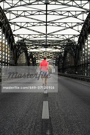 Young female runner crossing bridge