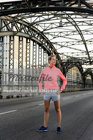 Young female runner exercising on bridge