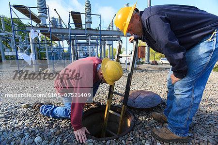 Power engineers placing ladder inside manhole at high voltage power distribution station, Braintree, Massachusetts, USA