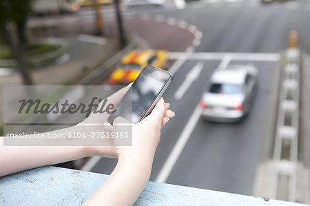 Young woman using smartphone on footbridge