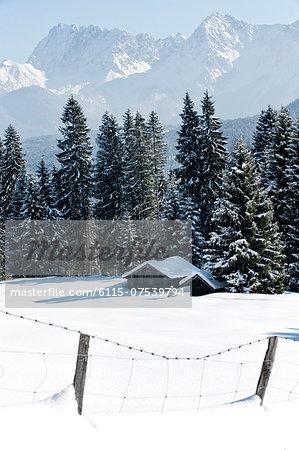 Log cabins in winter landscape, Garmisch, Bavaria, Germany