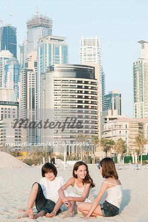 Siblings sitting together on beach, Dubai, United Arab Emirates
