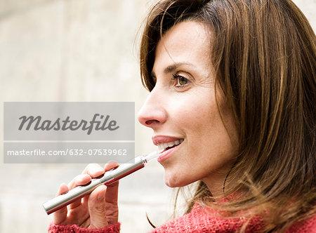 Woman smoking electronic cigarette, profile