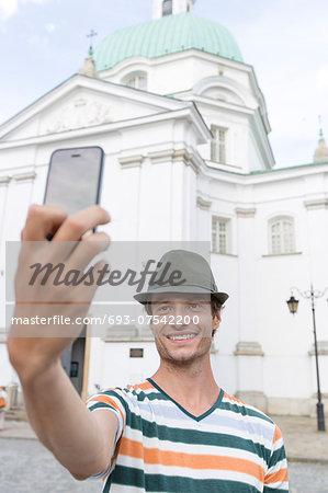 Young man taking self portrait outside St. Casimir Church, Warsaw, Poland