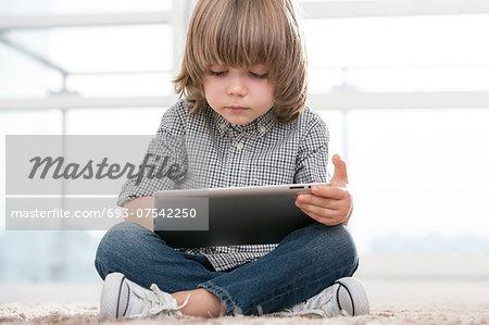 Full length of boy using digital tablet in living room