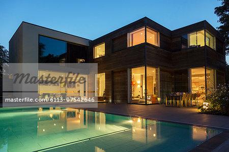 Modern house and swimming pool illuminated at dusk