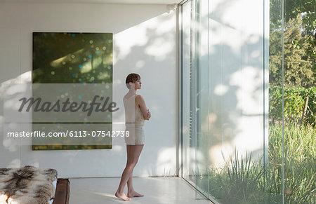 Woman standing at window in modern bedroom