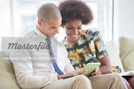 Business people using digital tablet on sofa