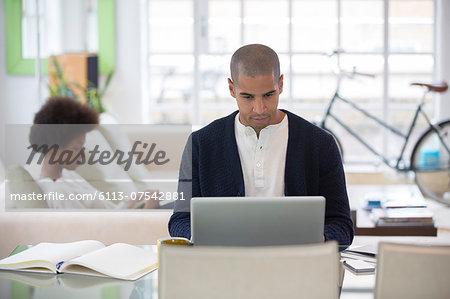 Man using laptop at desk in living room