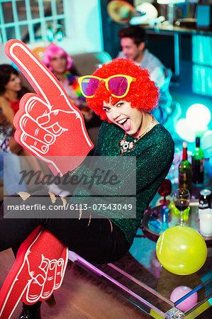 Woman wearing wig, oversized sunglasses and foam finger