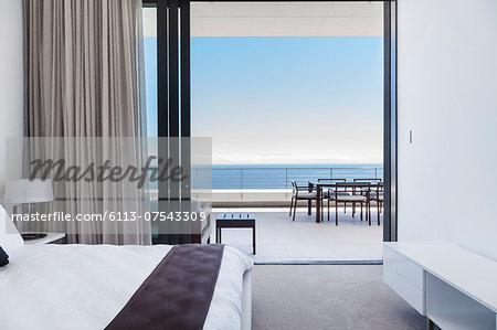 Modern bedroom and balcony overlooking ocean
