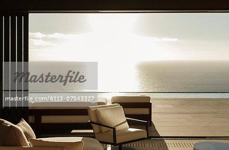 Modern living room overlooking ocean at sunset