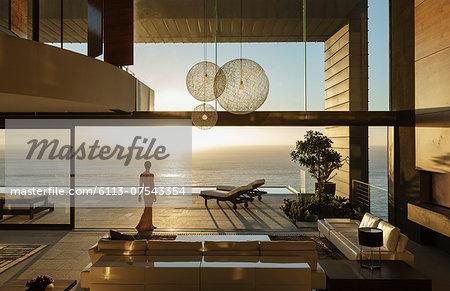 Woman in modern house overlooking ocean