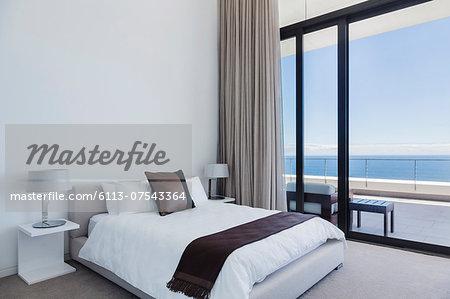 Bed and lamps in modern bedroom overlooking ocean