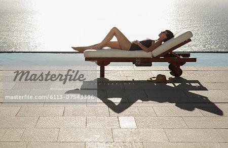 Woman sunbathing in lounge chair at poolside overlooking ocean