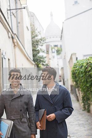 Businessmen walking on street near Sacre Coeur Basilica, Paris, France