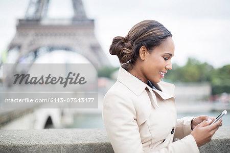 Businesswoman using cell phone near Eiffel Tower, Paris, France