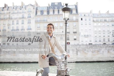 Businessman on bicycle along Seine River, Paris, France