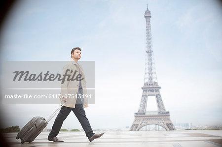Businessman pulling suitcase near Eiffel Tower, Paris, France